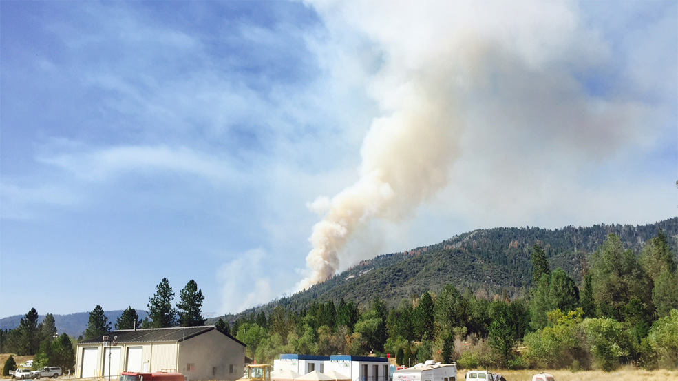 Picture of smoke billowing from  hillside at North Fork, with NF Fire department building in forefront