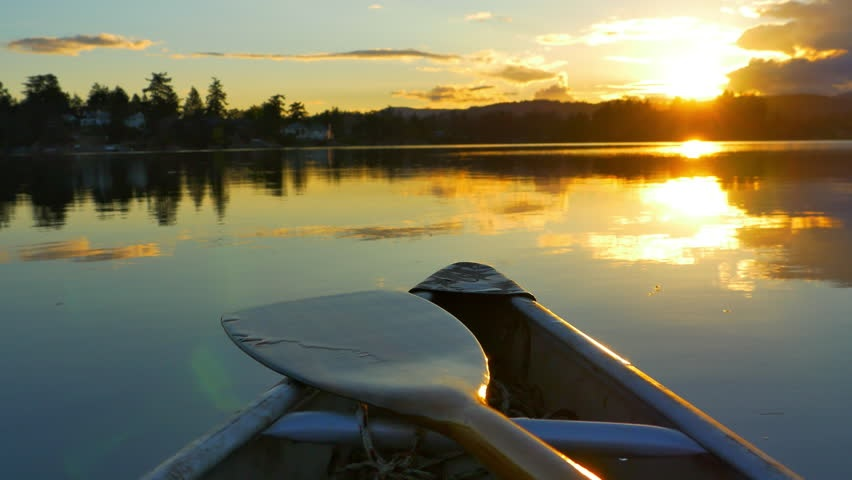 Image of canoe front and paddle with lake, trees and sunrise in background