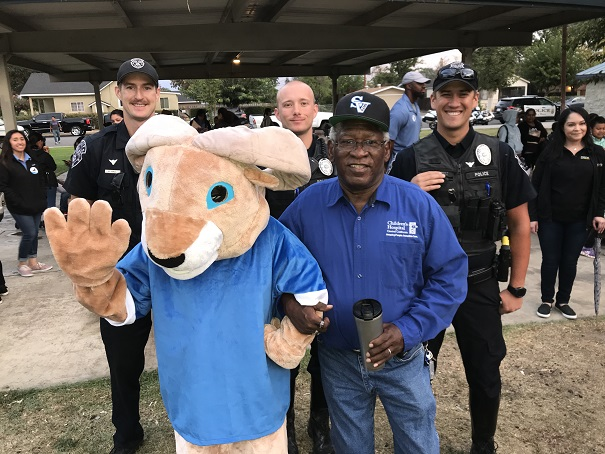 City Councilman Donald Holley and Madera Police Department Officers pose with the Sierra Vista Ram Mascot