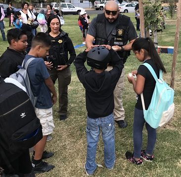 Madera County Probation Officers pass out stickers at McNally Park at
